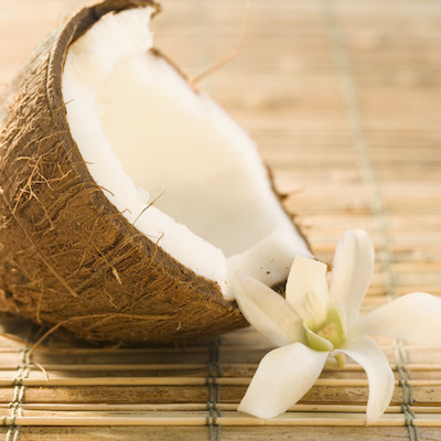 Half Coconut and Flower on Bamboo Mat