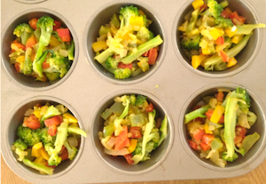 Muffin pan ready to go with an assortment of veggies: broccoli, peppers and pre-cooked onions
