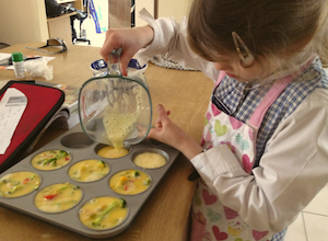 My niece Tamara helps to pour the beaten eggs into the muffin pan